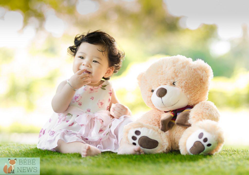 Une petite fille portant une robe à fleurs s'amuse avec son ours en peluche dans l'herbe
