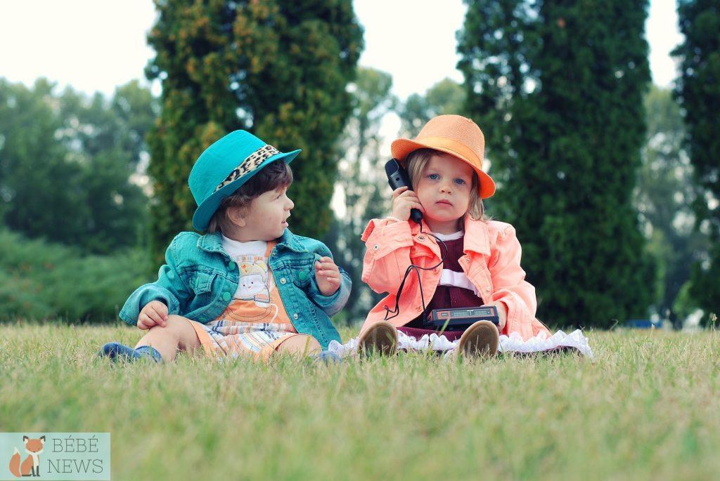 Un bébé portant un chapeau et une veste verte regarde un autre bébé portant un chapeau et une veste orange téléphoner